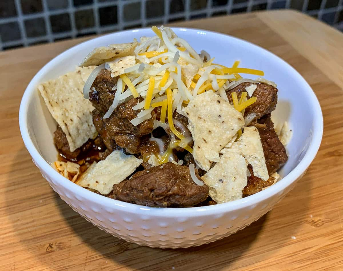 tex-mex chili with shredded cheese and tortilla chips