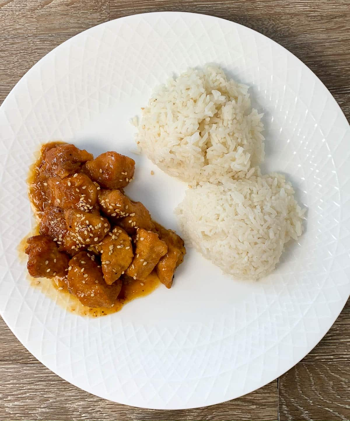overhead shot of orange chicken and white rice on a white plate