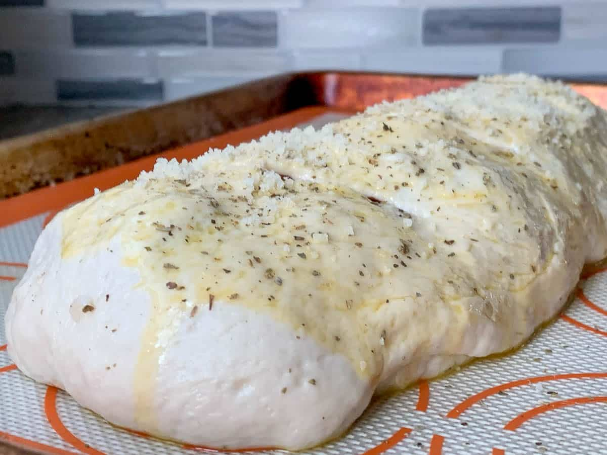 stromboli with parmesan and italian seasoning ready to be baked