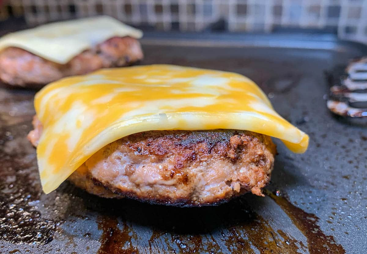 burger patty with cheese on grill